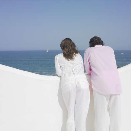bathingsuit: Couple looking over balconys edge