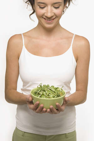 lower section view: Young woman holding a bowl of sprouts