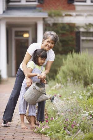 jubilado: Mujer y ni�a de las flores de riego LANG_EVOIMAGES