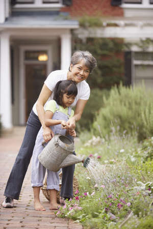 family gardening: Woman and girl watering flowers