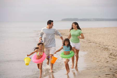ni�os latinos: Familia caminando en la playa