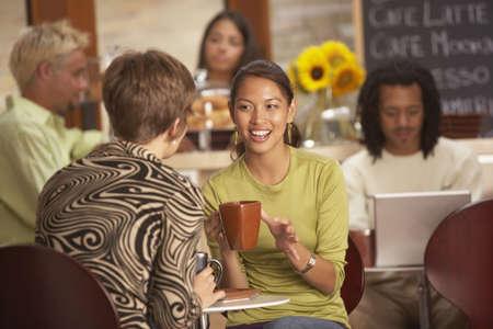 tend: Women talking in coffee house
