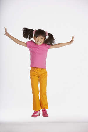 light hearted: Portrait of girl jumping with arms out LANG_EVOIMAGES
