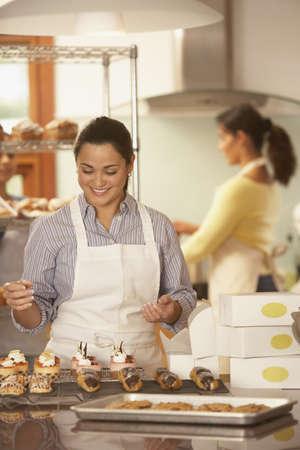 prodotti da forno: Donna che decora prodotti da forno a forno LANG_EVOIMAGES