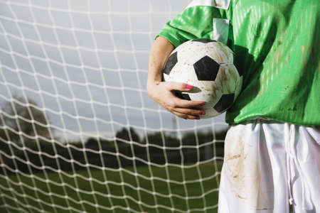 lower section: Lower section of girl holding soccer ball