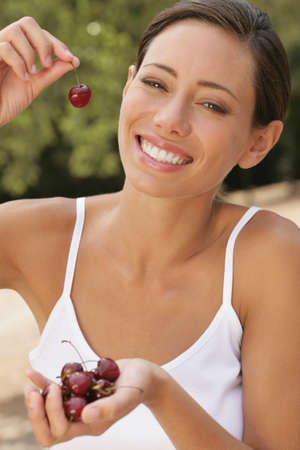 casualness: Young woman smiling with cherries