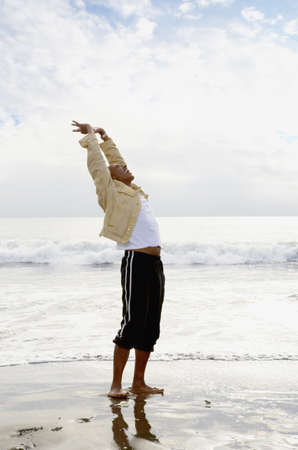 longshot: Side view of man stretching at beach