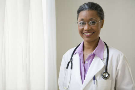 lass: African American doctor standing and smiling