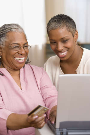 ninetys: Mother and daughter with laptop and credit card LANG_EVOIMAGES