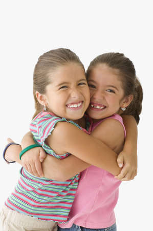 two girls hugging: Portrait of two girls hugging LANG_EVOIMAGES