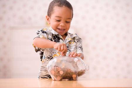 niÑos contentos: Muchacho joven que pone dinero en la hucha