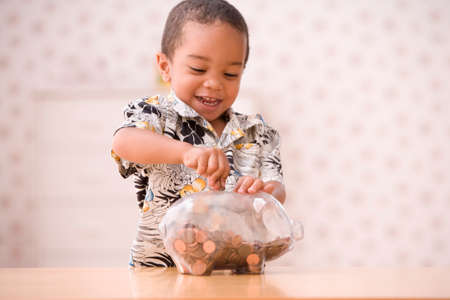 african children: Young boy putting money in piggy bank