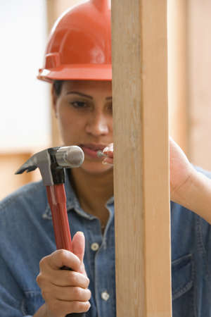 thirtys: Female construction worker hammering nail into framework