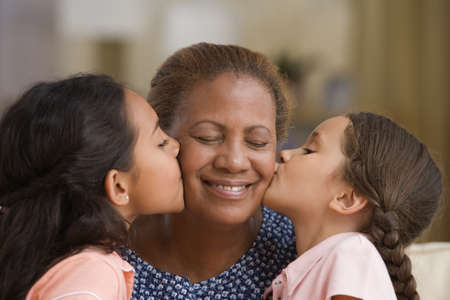 grandmother grandchild: Daughters kissing each of their mothers cheeks LANG_EVOIMAGES