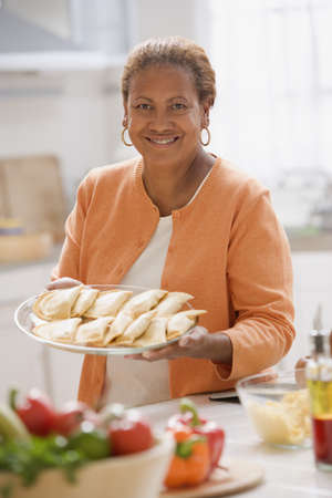 gramma: Woman holding out a plate of dumplings