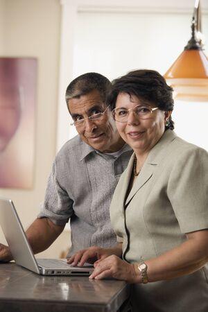 ノート パソコンと成熟したカップルの肖像画 写真素材