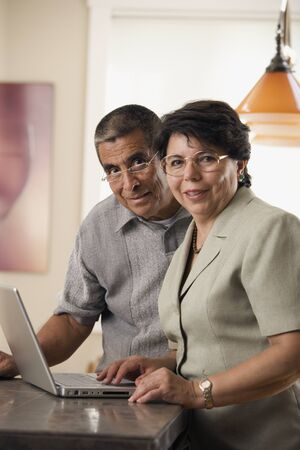 Portrait of mature couple with laptop Imagens