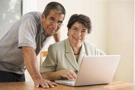 Portrait of mature couple with laptop Imagens