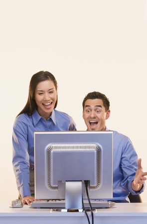 jesting: Businesspeople laughing at computer screen