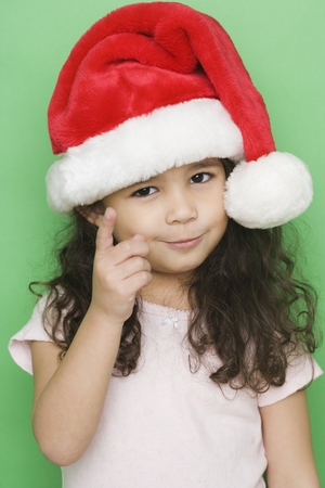 vibrating: Portrait of girl wearing santa hat and pointing LANG_EVOIMAGES