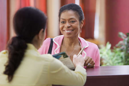 ninetys: Woman talking to a receptionist LANG_EVOIMAGES