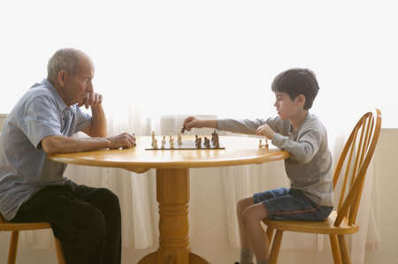 Side view of boy playing chess with elderly man