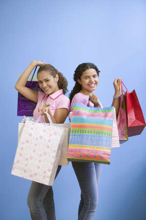 shopping buddies: Portrait of  two teenage girls holding gift bags