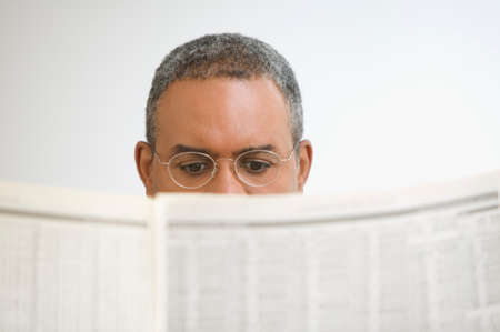 Close up of mature man reading newspaper
