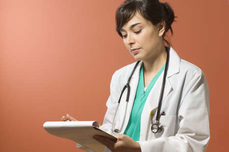 doctor writing: Female doctor writing notes LANG_EVOIMAGES