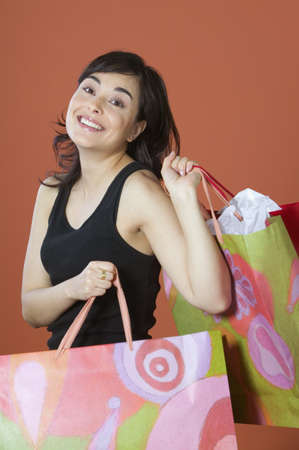 mischievious: Portrait of woman carrying shopping bags