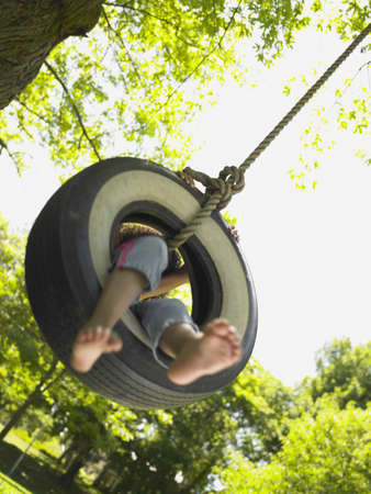 Barefoot girl on tire swing Stock Photo