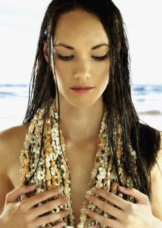 above 18: Young woman wearing shells over her chest LANG_EVOIMAGES