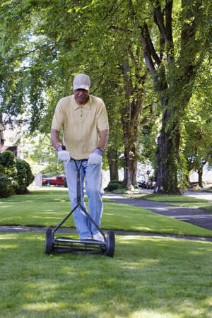 only mid adult men: Middle-aged man mowing the lawn LANG_EVOIMAGES