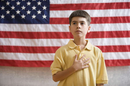 low spirited: Boy in front of American flag with hand over heart LANG_EVOIMAGES