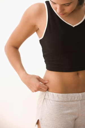 bellybutton: Teenager pinching fat on side of stomach