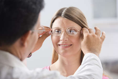 solicitous: Male doctor fitting glasses on woman