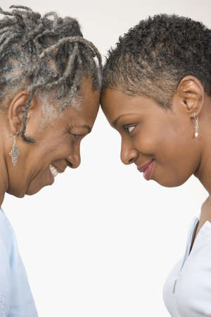 elderly adults: Close up profile of mother and daughter looking at each other