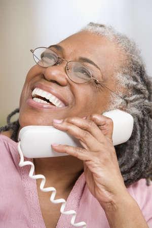 personas comunicandose: Cerca de la mujer adulta de alto riendo en el tel�fono LANG_EVOIMAGES