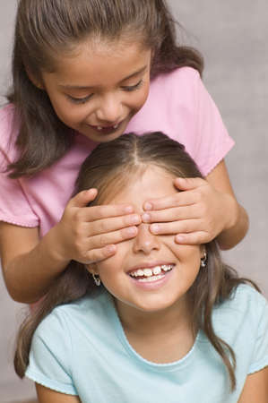 Girl with hands over another girlís face Stock Photo