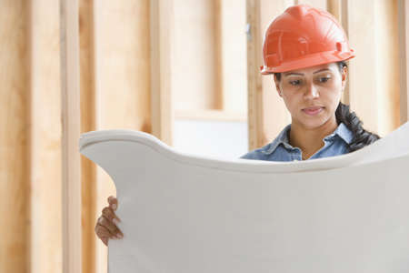 Female construction worker reading plans LANG_EVOIMAGES