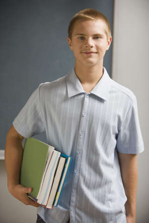 toiling: Student with schoolbooks smiling for the camera LANG_EVOIMAGES