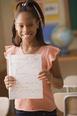 schoolroom: Young girl showing off test score of 100