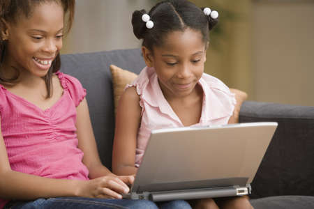 elementary age girls: Young girls using a laptop together LANG_EVOIMAGES