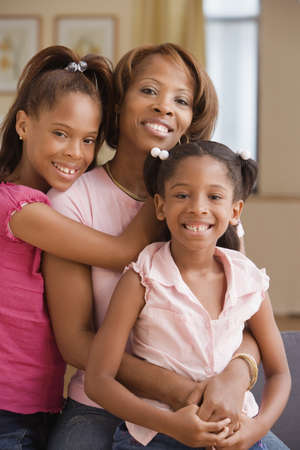 adoring: Mother and daughters smiling for the camera
