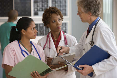 woman serious: Doctors and nurse talking