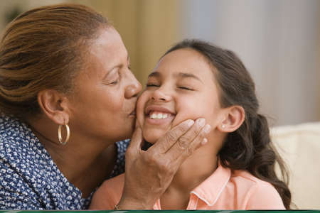 abrazar familia: Madre besando la mejilla de su hija