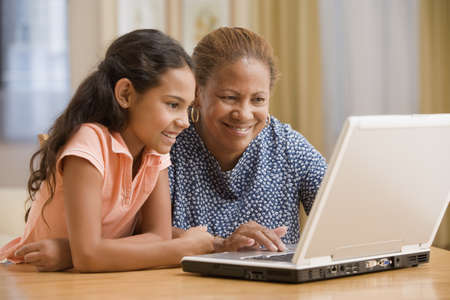 hispanic people: Mother and daughter using computer together LANG_EVOIMAGES