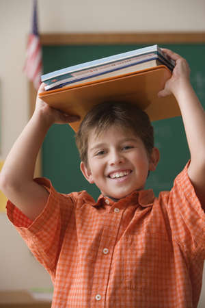 gratifying: Young boy holding books on his head