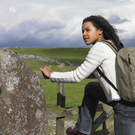 adventuresome: Young woman climbing a stone fence