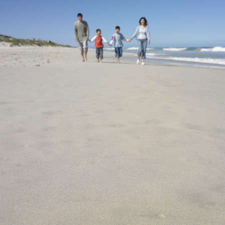 longshot: Family walking and holding hands on the beach LANG_EVOIMAGES